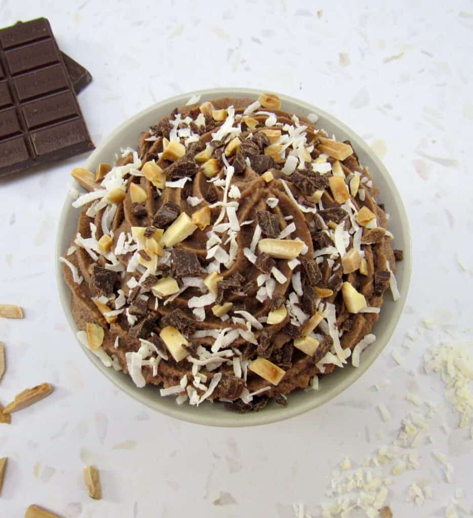 overhead view of bowl of chocolate mousse with coconut and almonds on top