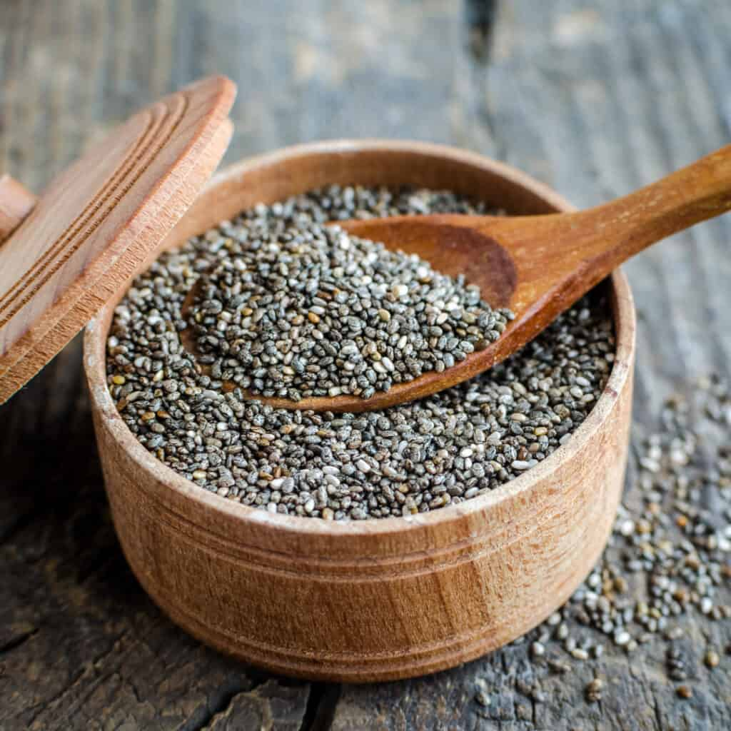 Chia Seeds in wooden bowl with wooden spoon in it
