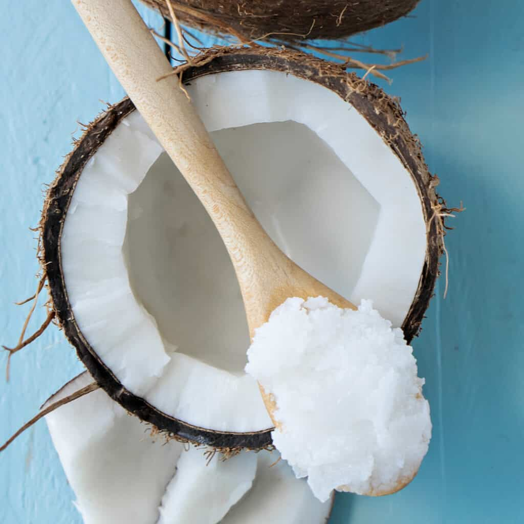 Coconut Oil in wooden spoon sitting on open coconut