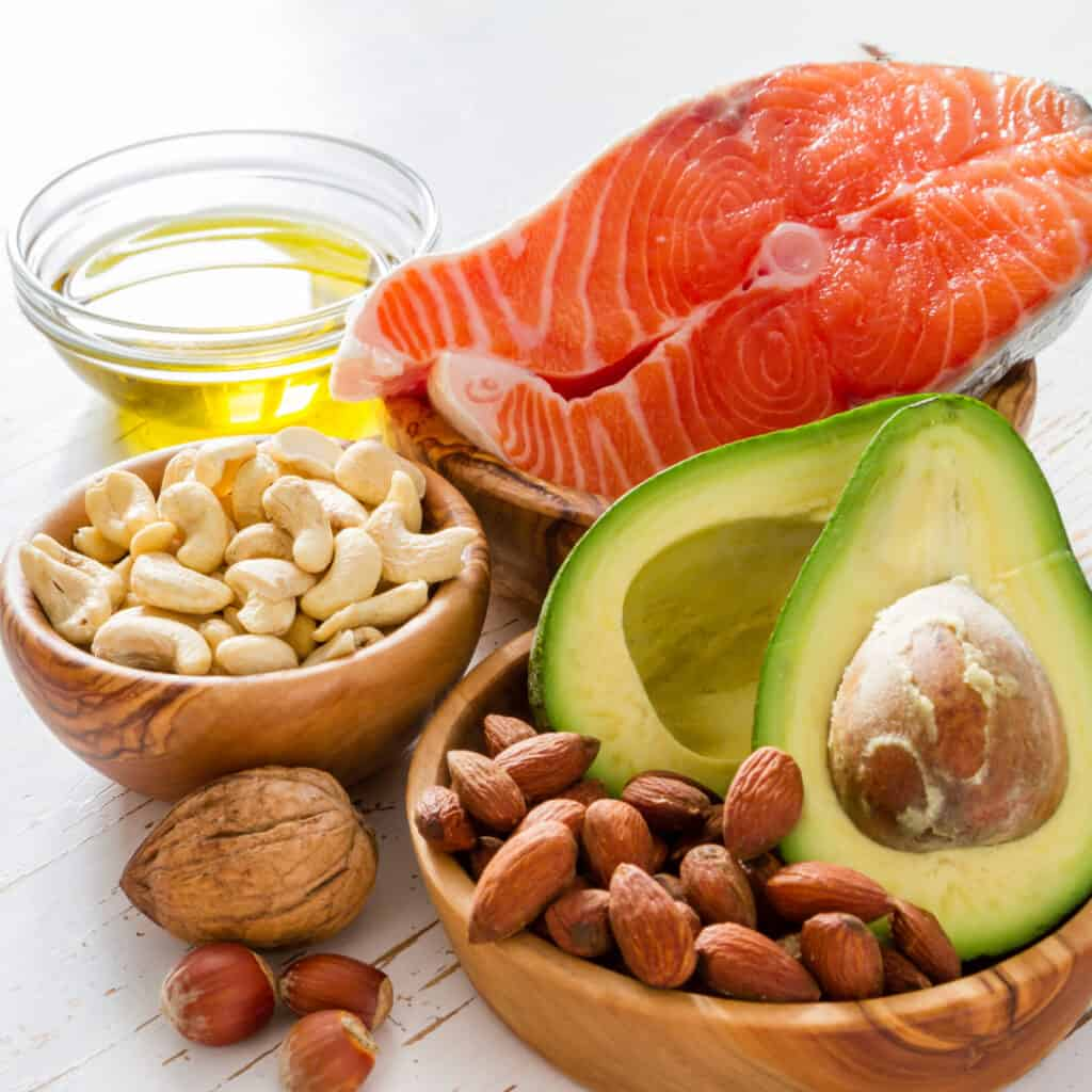 avocado, nuts and salmon in wooden bowls