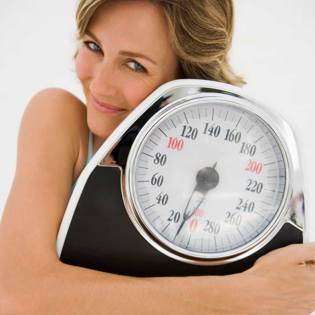 woman hugging a scale