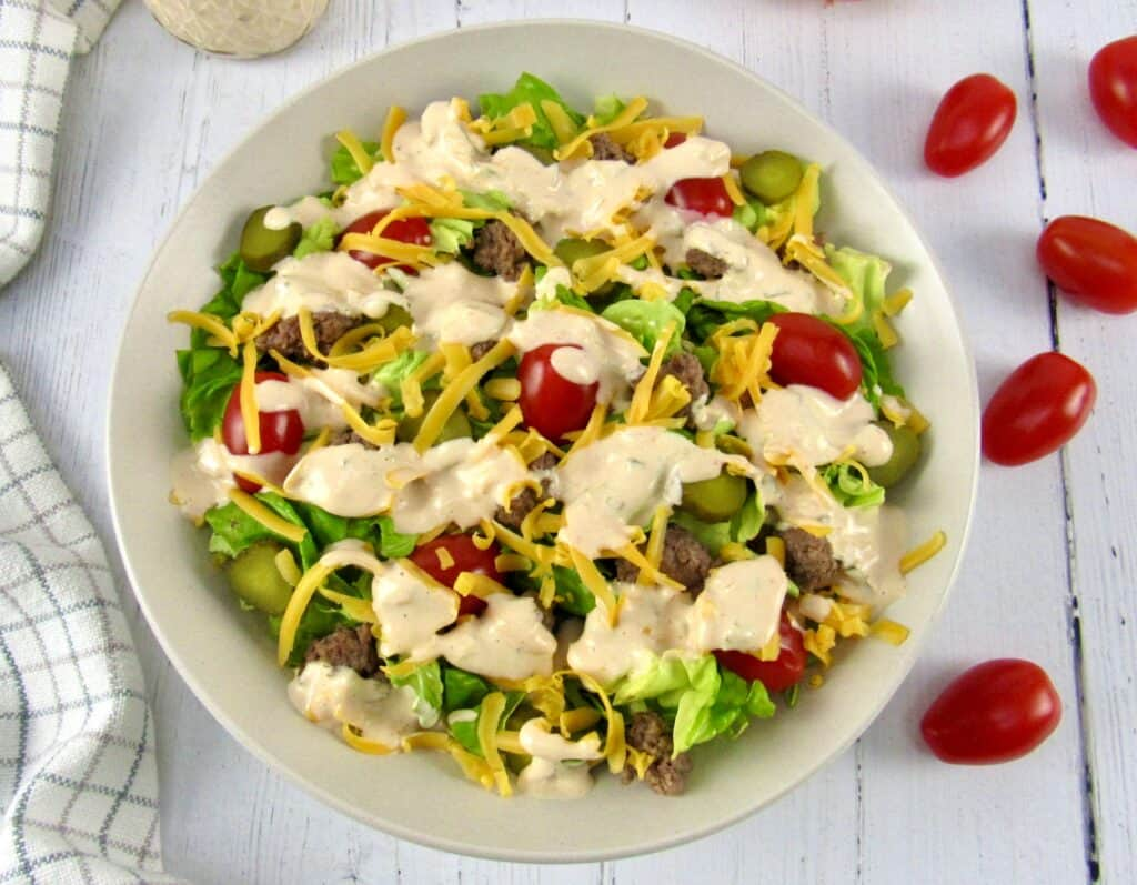 overhead view of cheeseburger salad with tomatoes on side