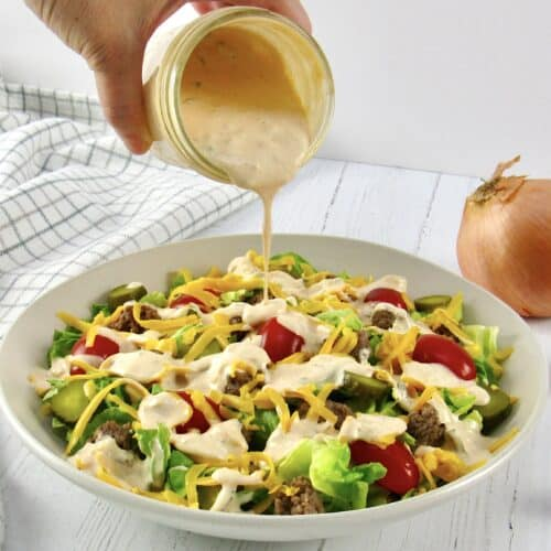 cheeseburger salad with dressing being poured over the top