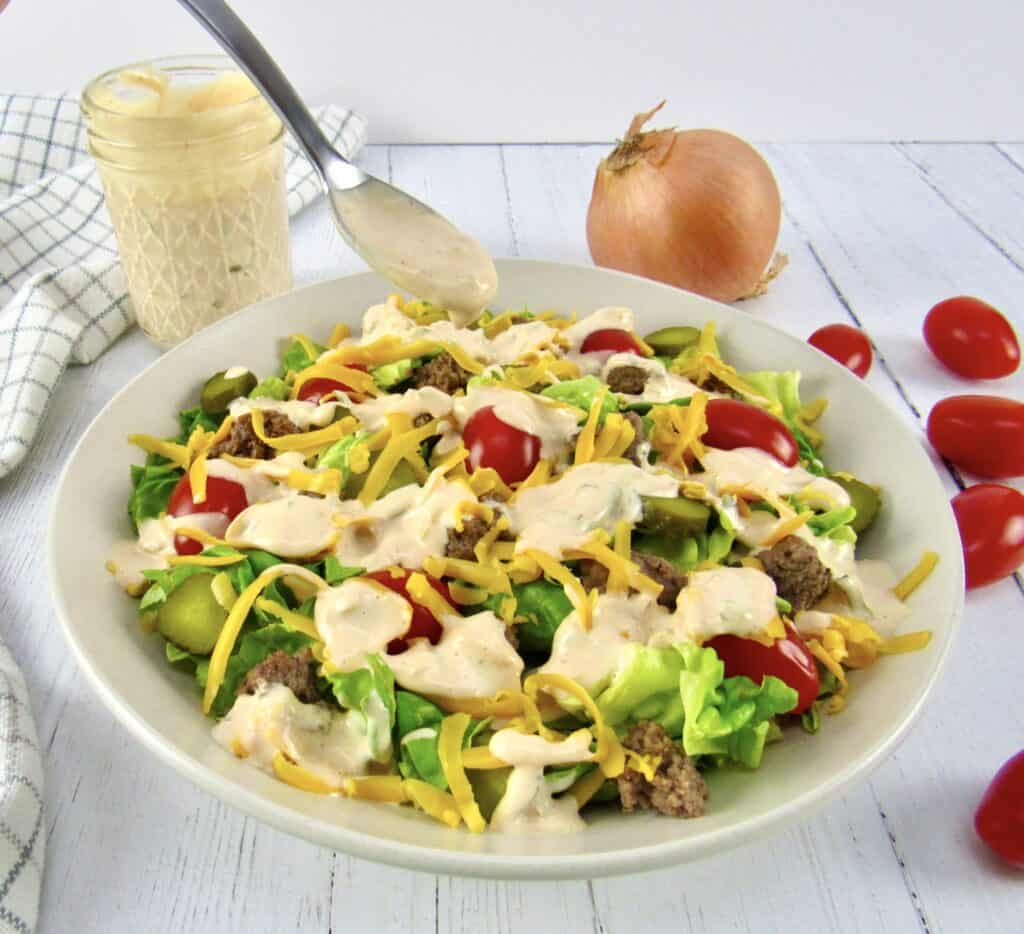 cheeseburger salad with spoon dripping dressing on top