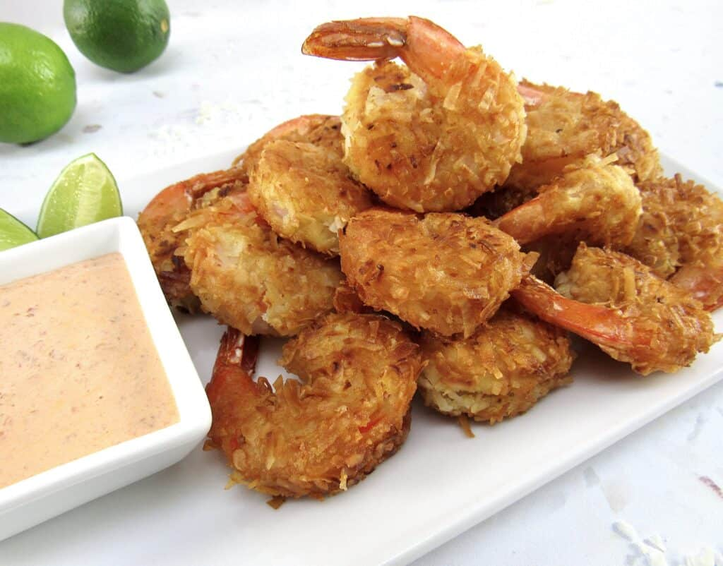coconut shrimp piled up on plate with dish of dipping sauce on side