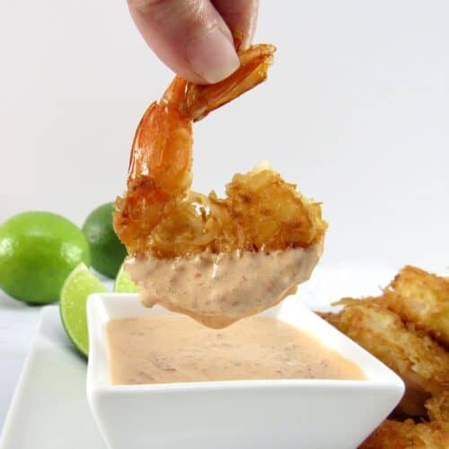 coconut shrimp being dipped into sauce