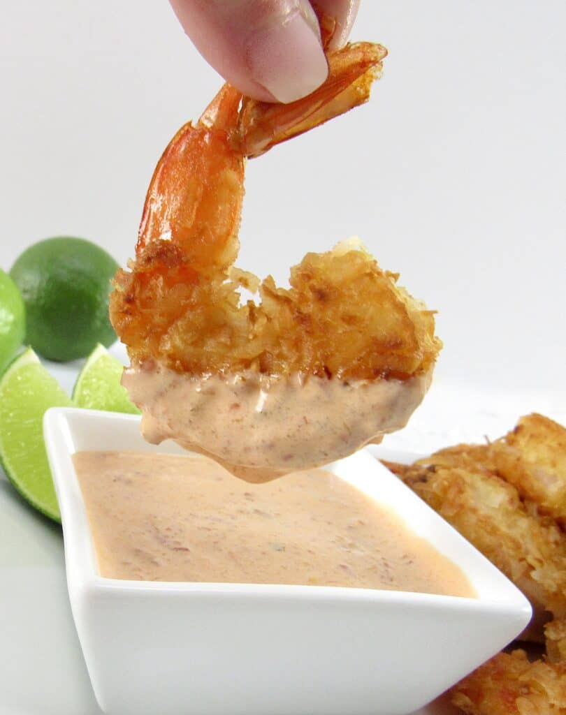 coconut shrimp being dipping into sauce