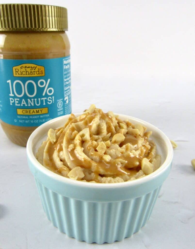 closeup of peanut butter mousse in turquoise ramekin with crazy richard's peanut butter in background