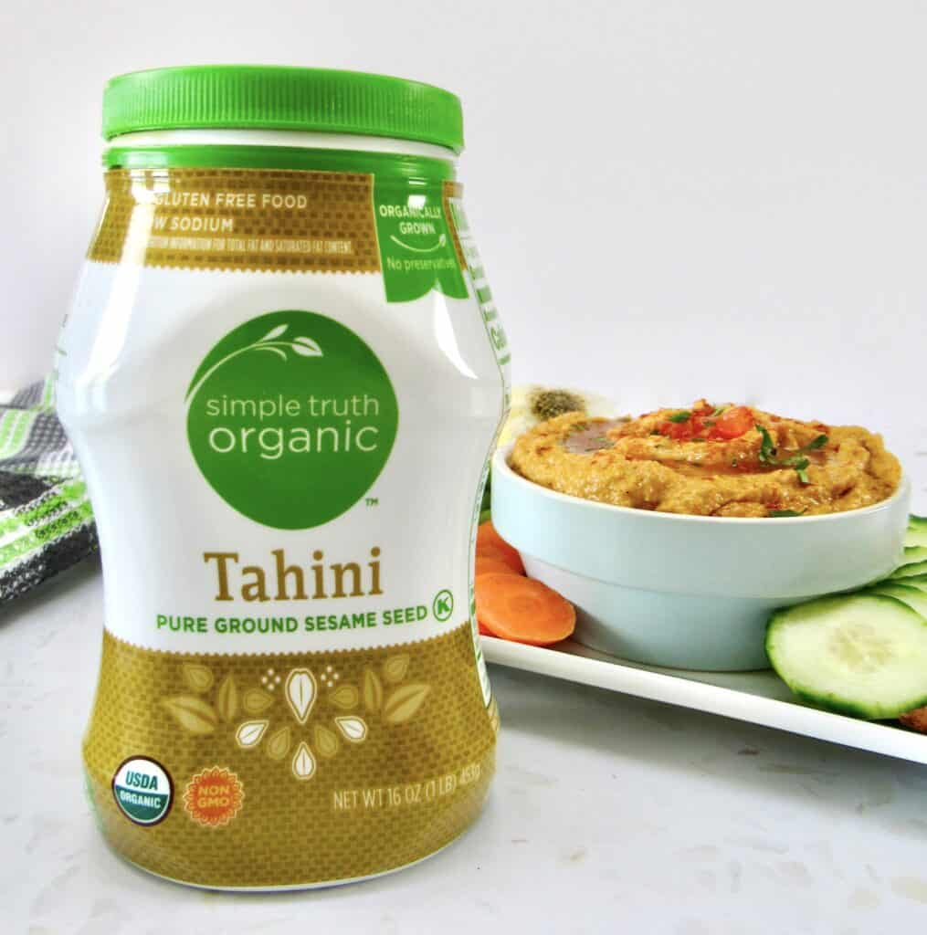closeup of jar of tahini with hummus in background