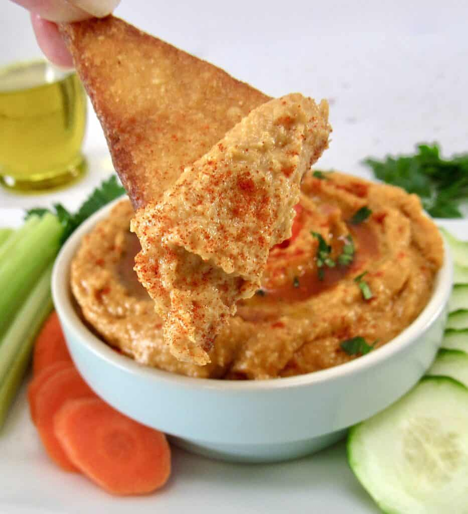 tortilla chip being dipped into hummus
