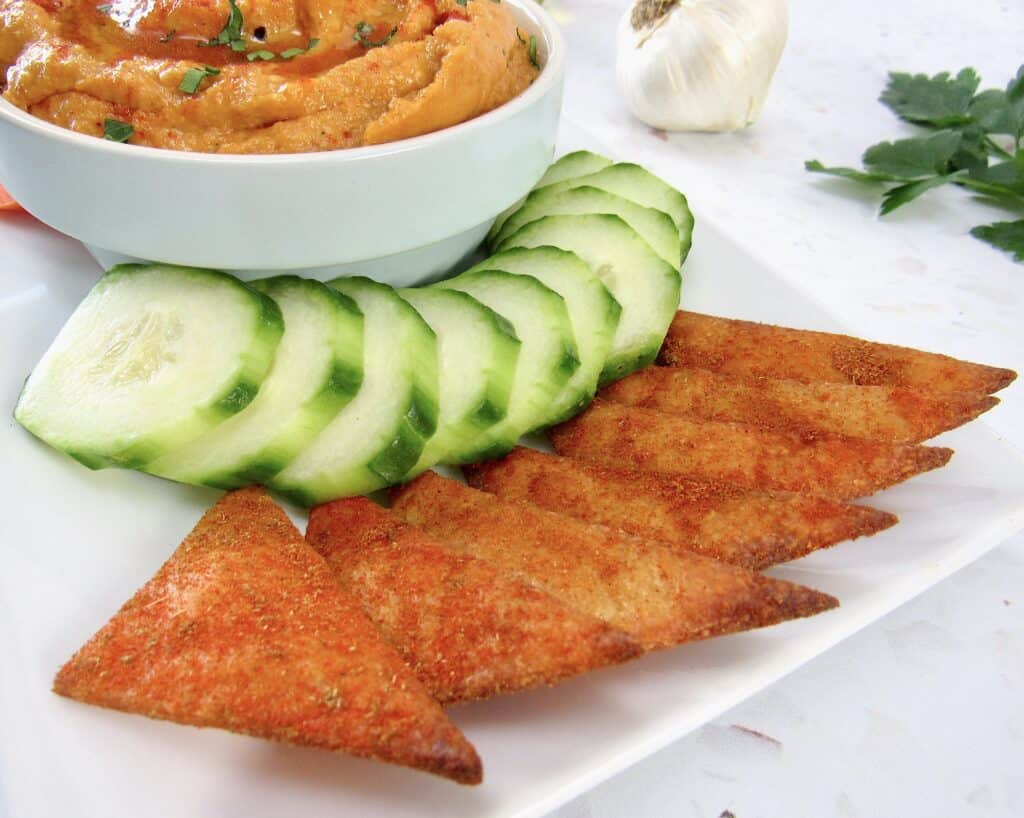 tortilla chips on platter with hummus and sliced cucumber