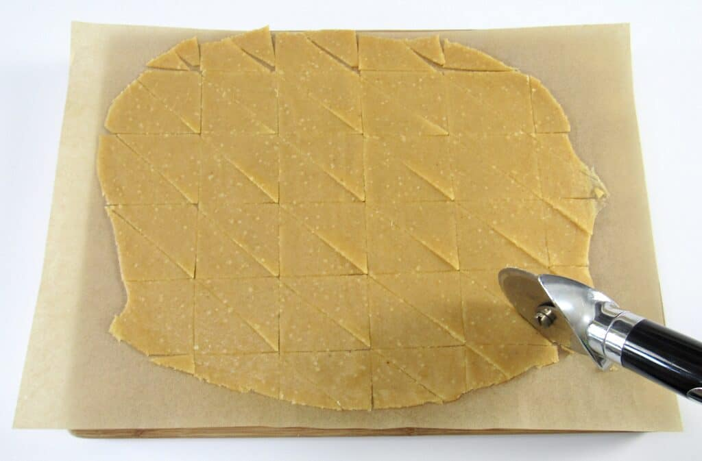 tortilla chips dough being cut into triangles