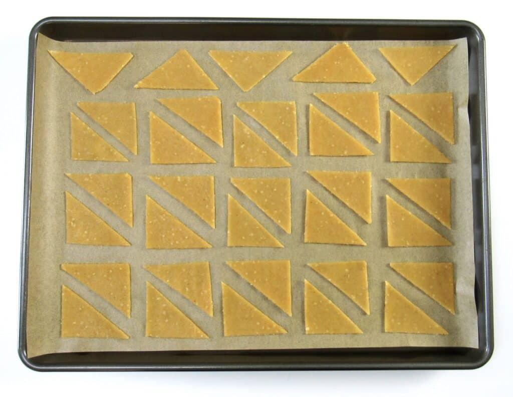 tortilla chips dough cut into triangles on baking sheet
