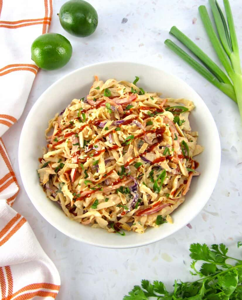 overhead view of spicy coleslaw in bowl with scallions and limes