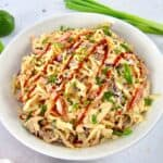 spicy coleslaw in bowl with sauce on top