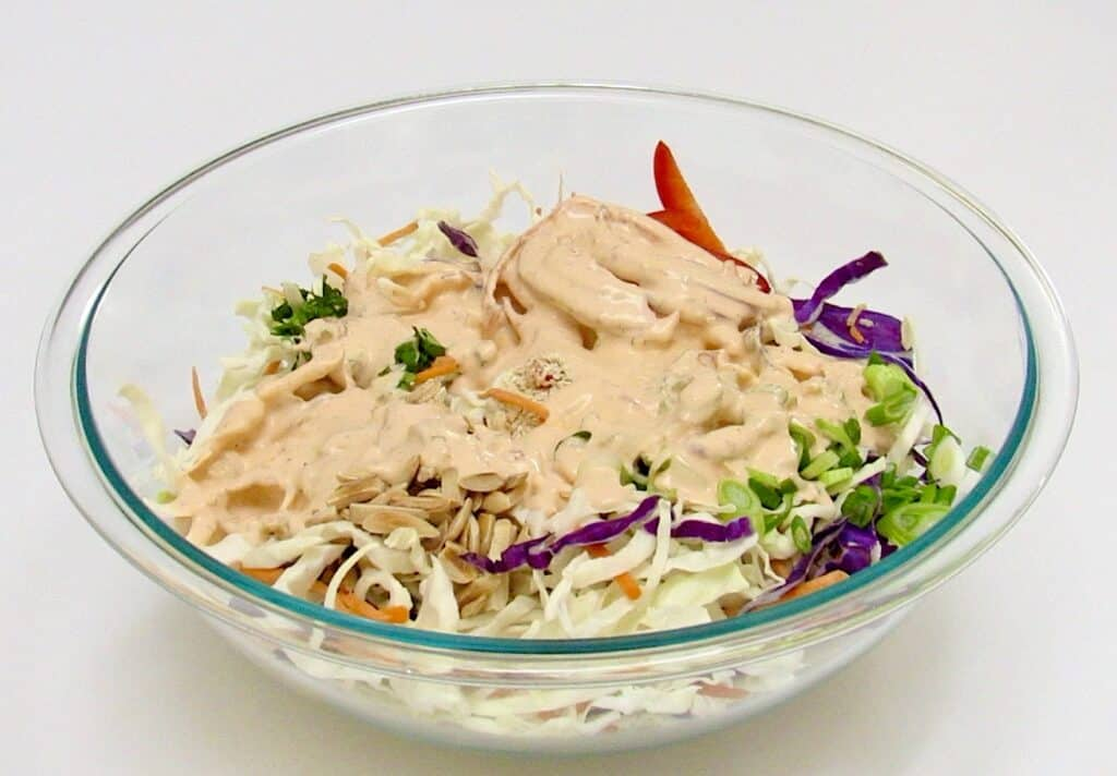 coleslaw ingredients in glass bowl unmixed with sauce on top