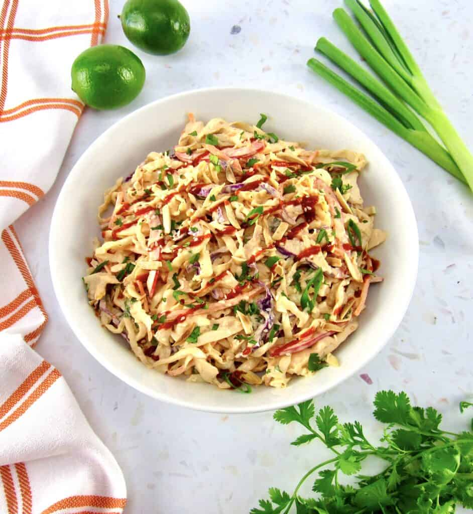 spicy coleslaw in white bowl with limes and scallions on the side