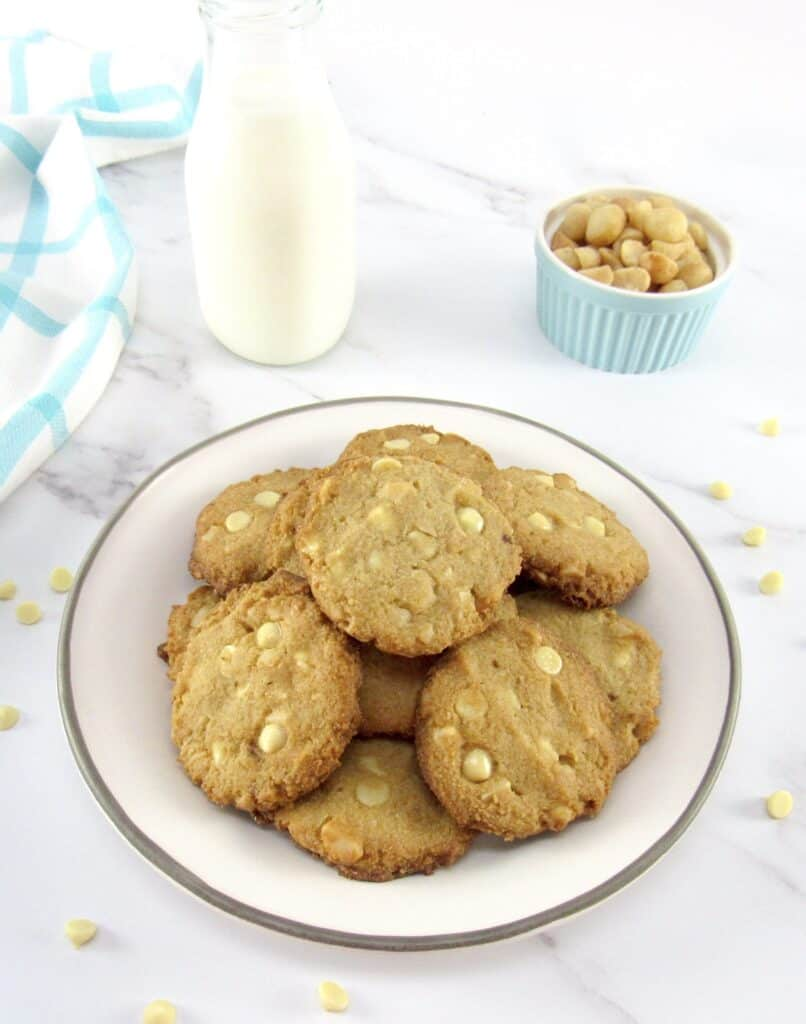 pile of white chocolate macadamia nut cookies on plate with milk in background