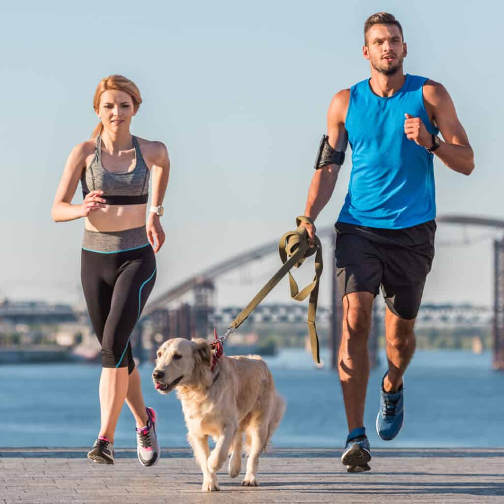 man and woman jogging with dog