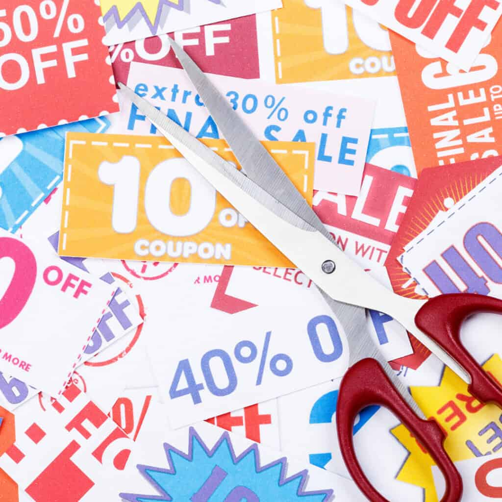 pile of coupons with a pair of red scissors on top