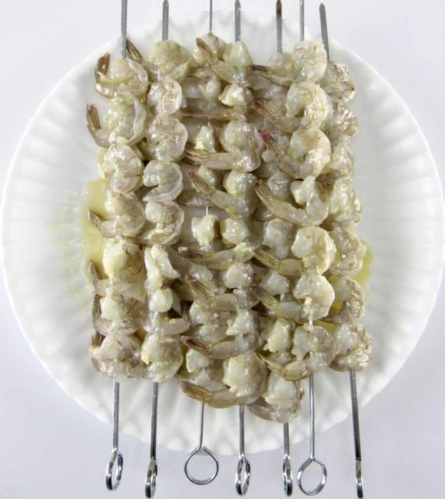 raw shrimp on skewers on white plate