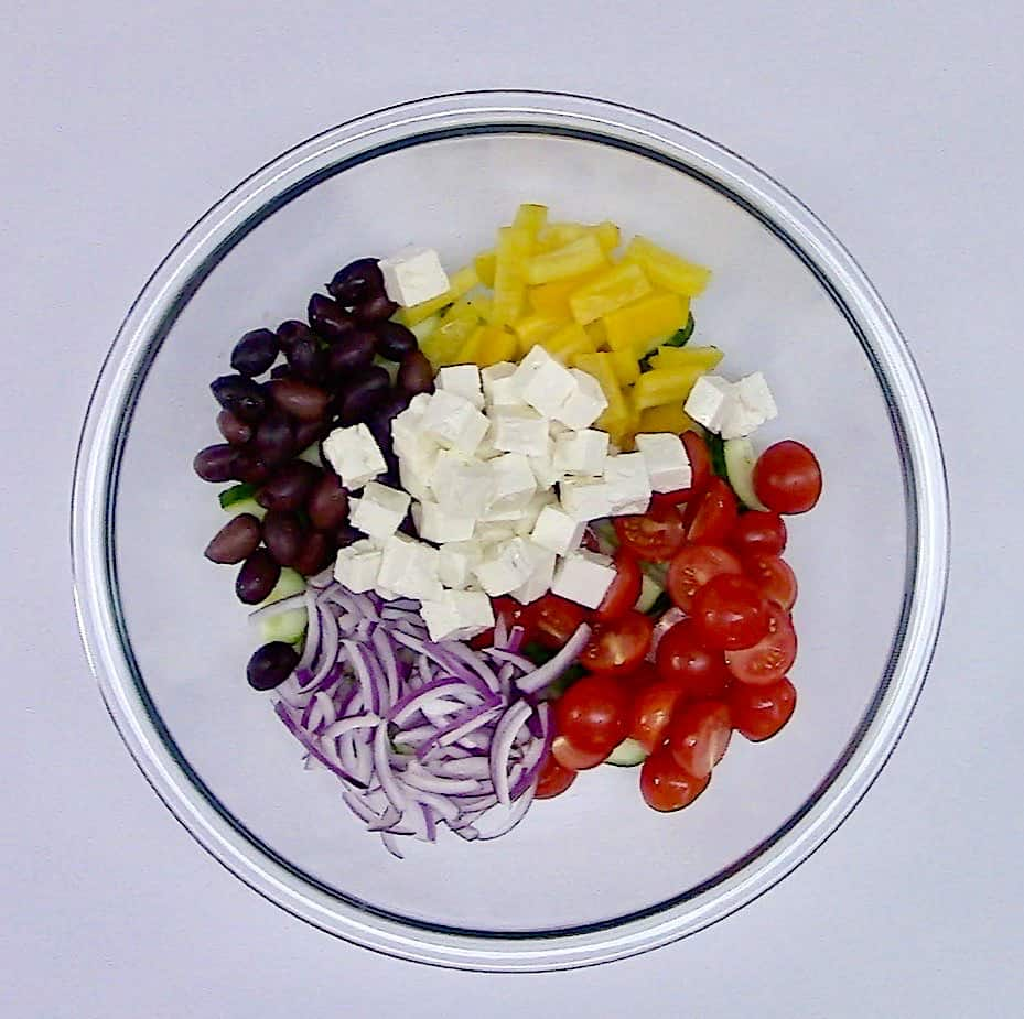 greek salad ingredients in glass bowl