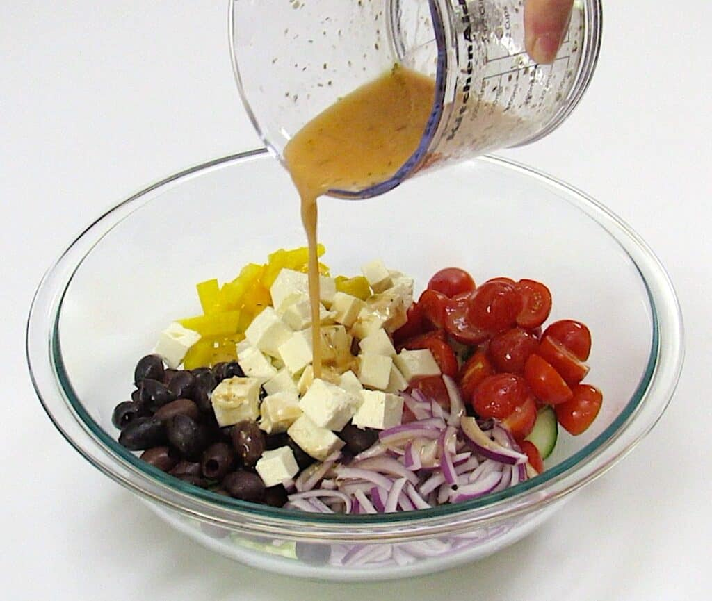 salad dressing being poured over greek salad