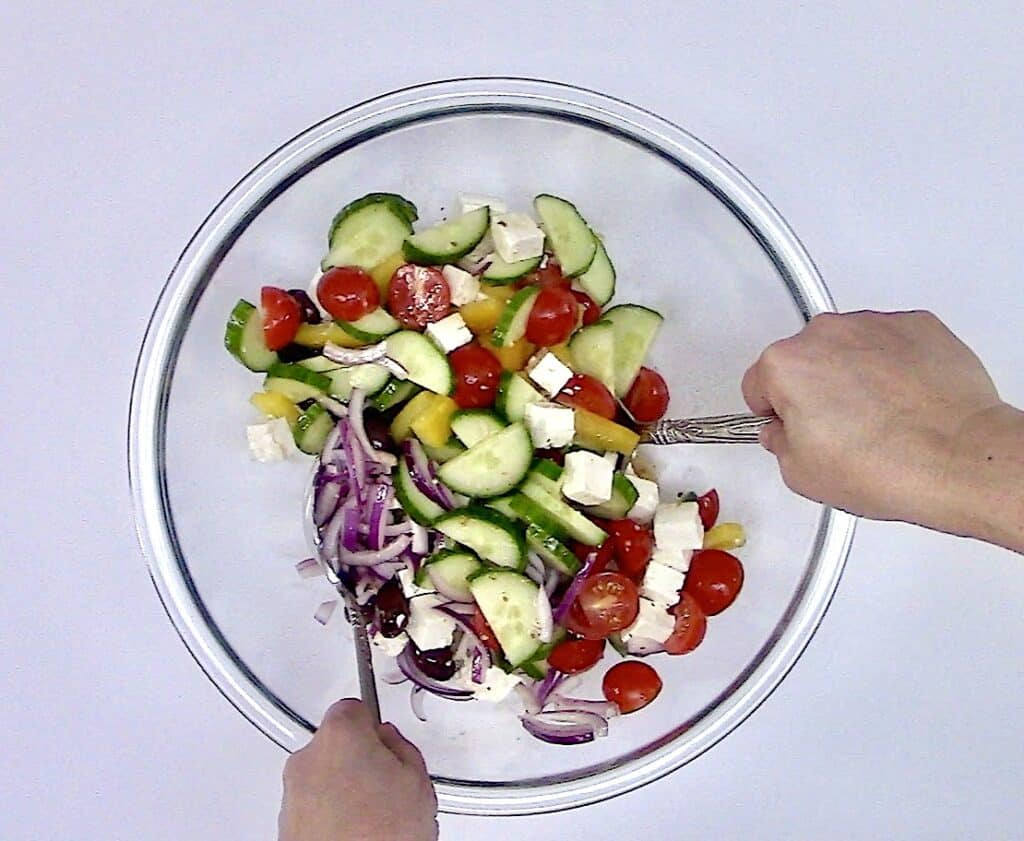 greek salad being toss with 2 silver spoons
