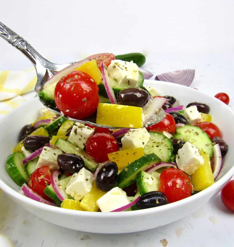 greek salad in white bowl with spoon holding some up