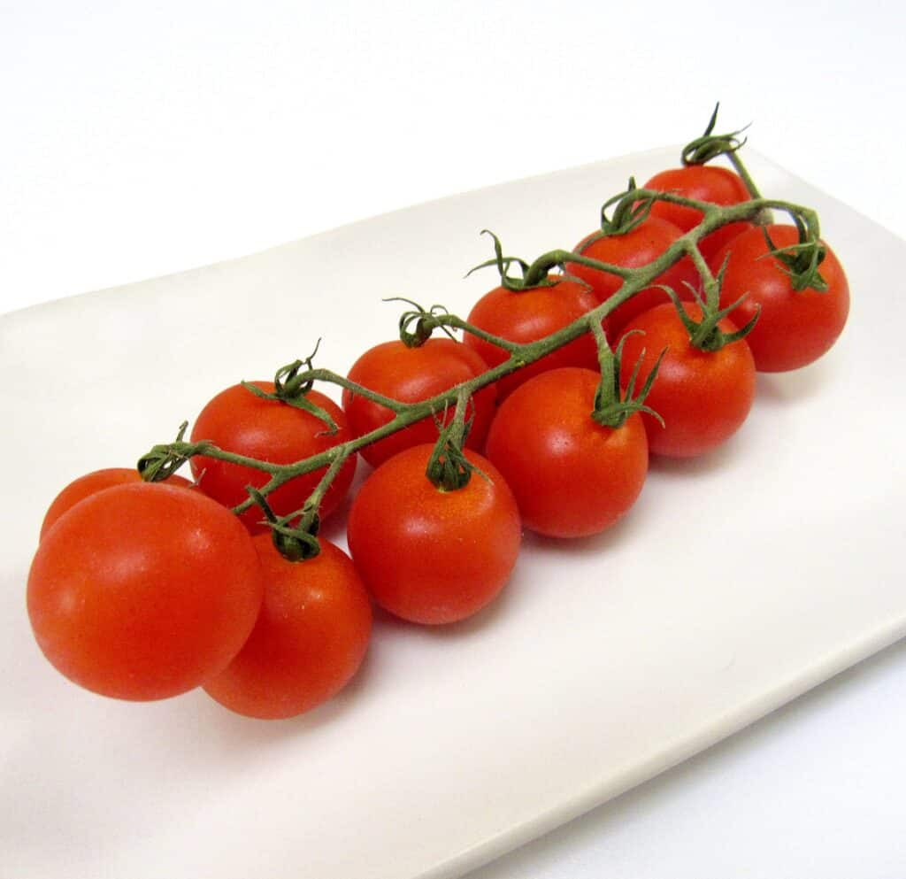 vine of cherry tomatoes on white plate