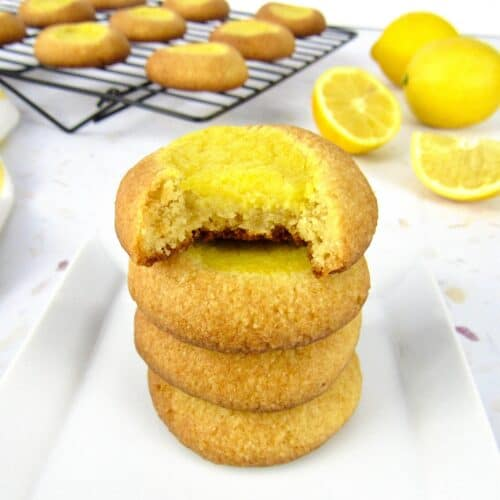 lemon curd thumbprint cookies stacked on white plate with bite taken out of one