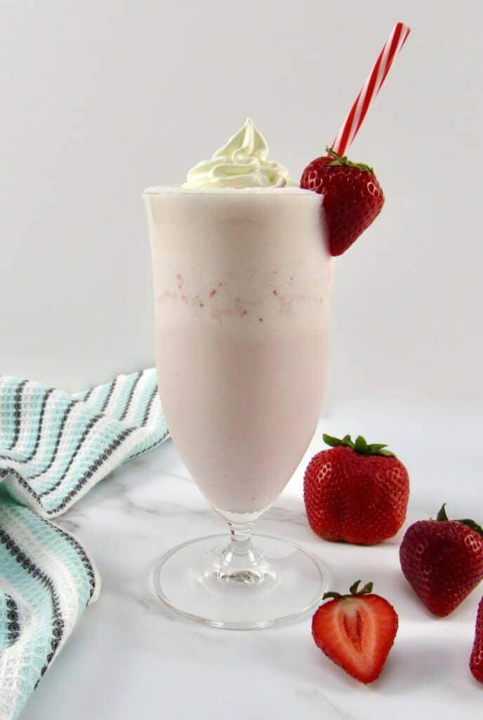 side view of strawberry smoothie with whip cream and strawberry on glass