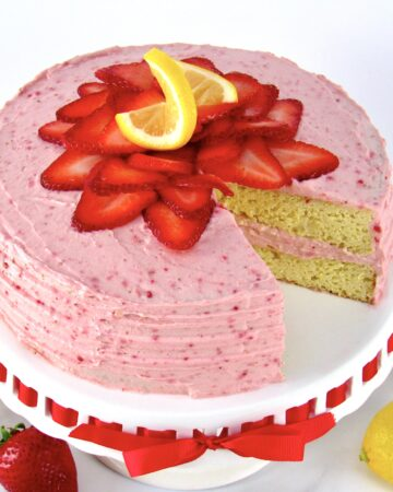 strawberry cake on cake stand with strawberries on top with slice missing