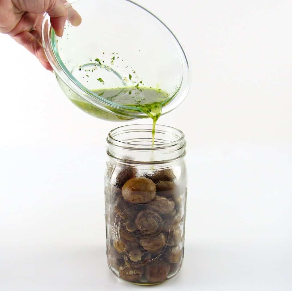mushrooms in canning jar with marinade being poured over the top