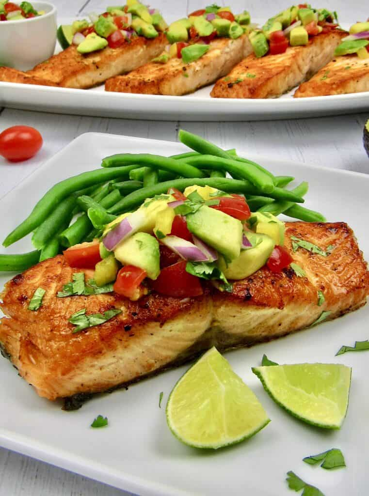 piece of salmon on white plate with salsa on top and green beans on the side