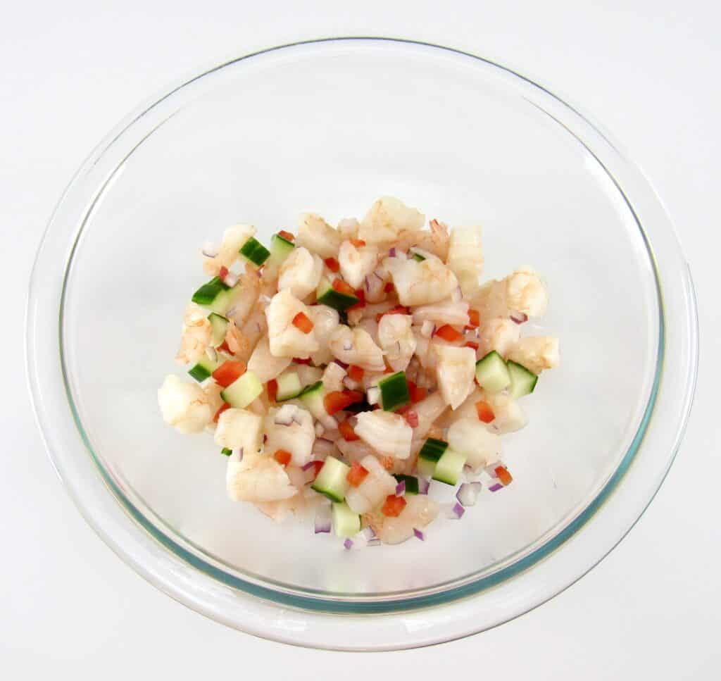 glass bowl with shrimp red pepper red onion and cucumber mixed up