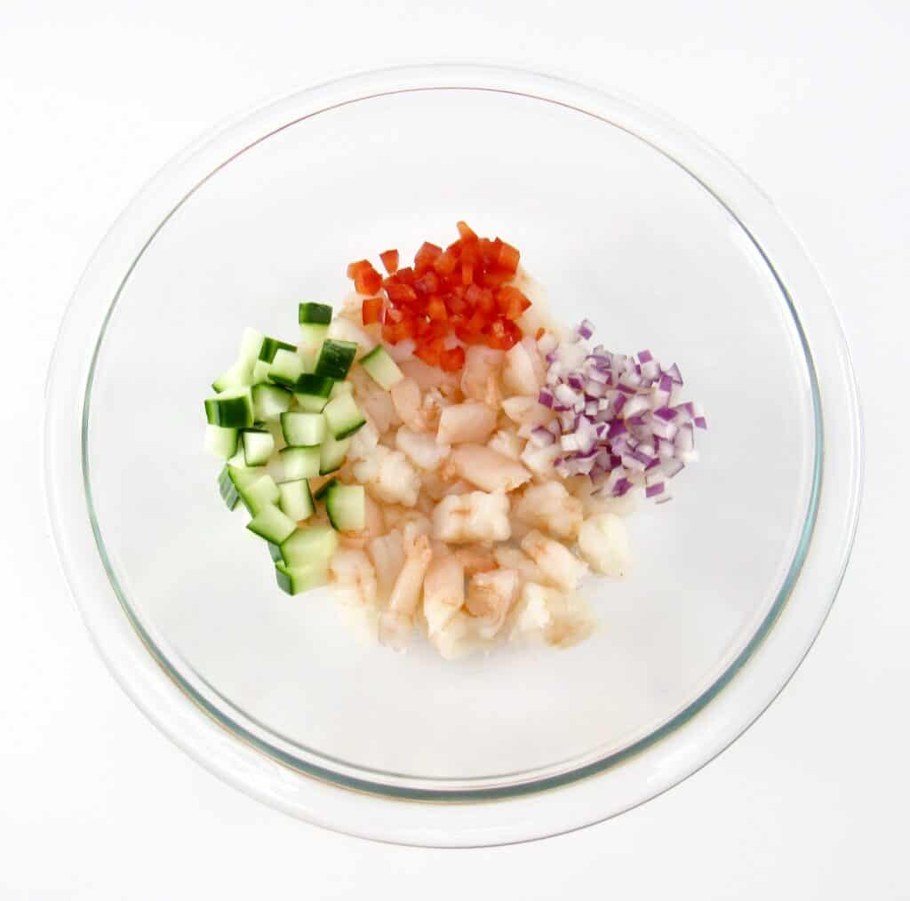 glass bowl with shrimp red pepper red onion and cucumber