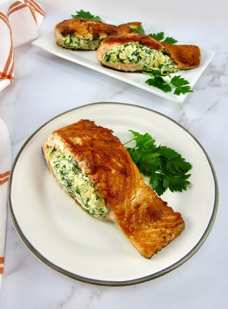 stuffed salmon on plate with parsley with more on plate in background