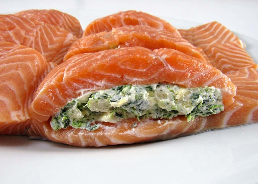 raw salmon with spinach artichoke mix stuffed inside