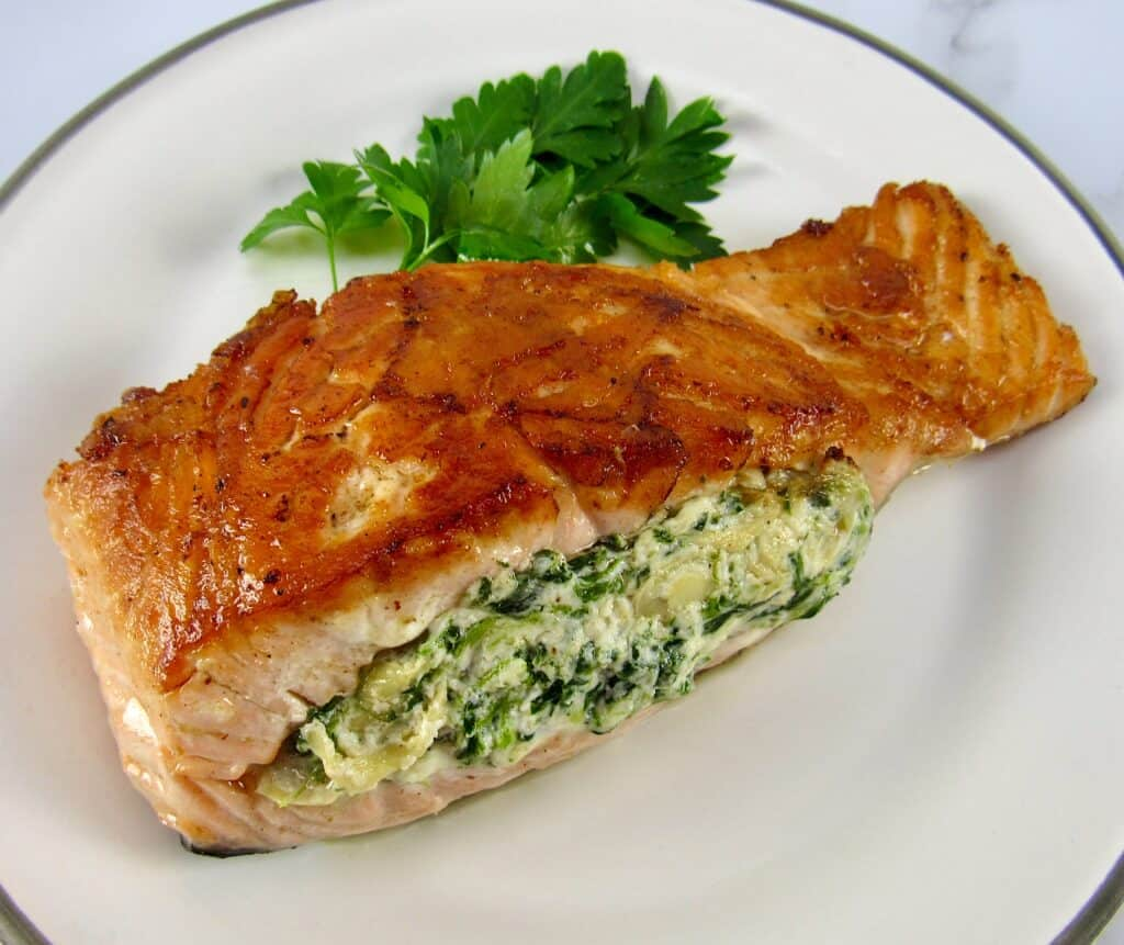 overhead view of stuffed salmon on plate with parsley