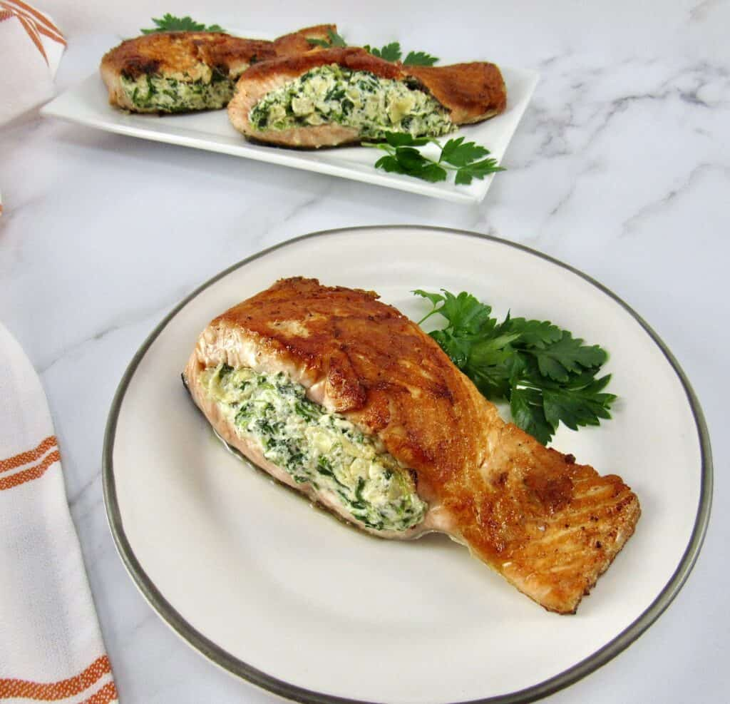 stuffed salmon on plate with parsley and more in background