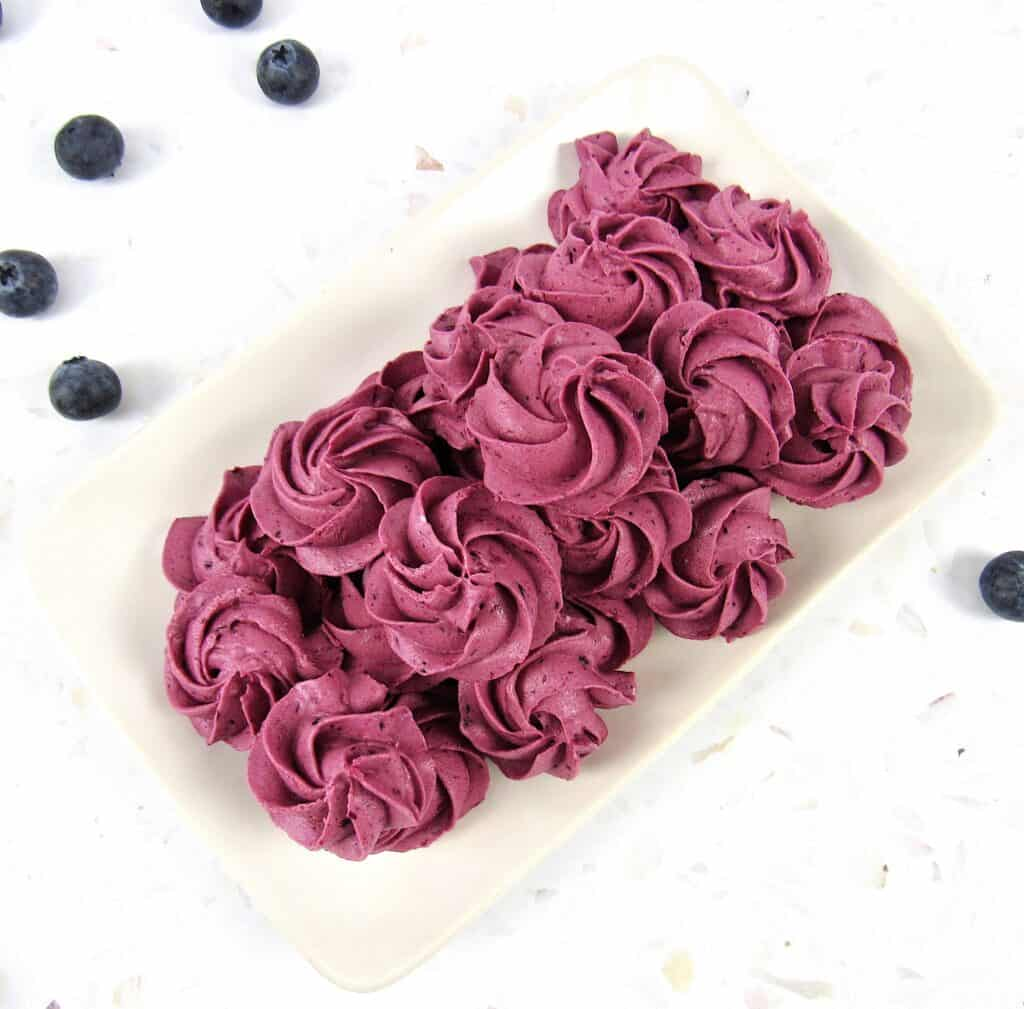 overhead view of blueberry fat bomb rosettes on beige plate