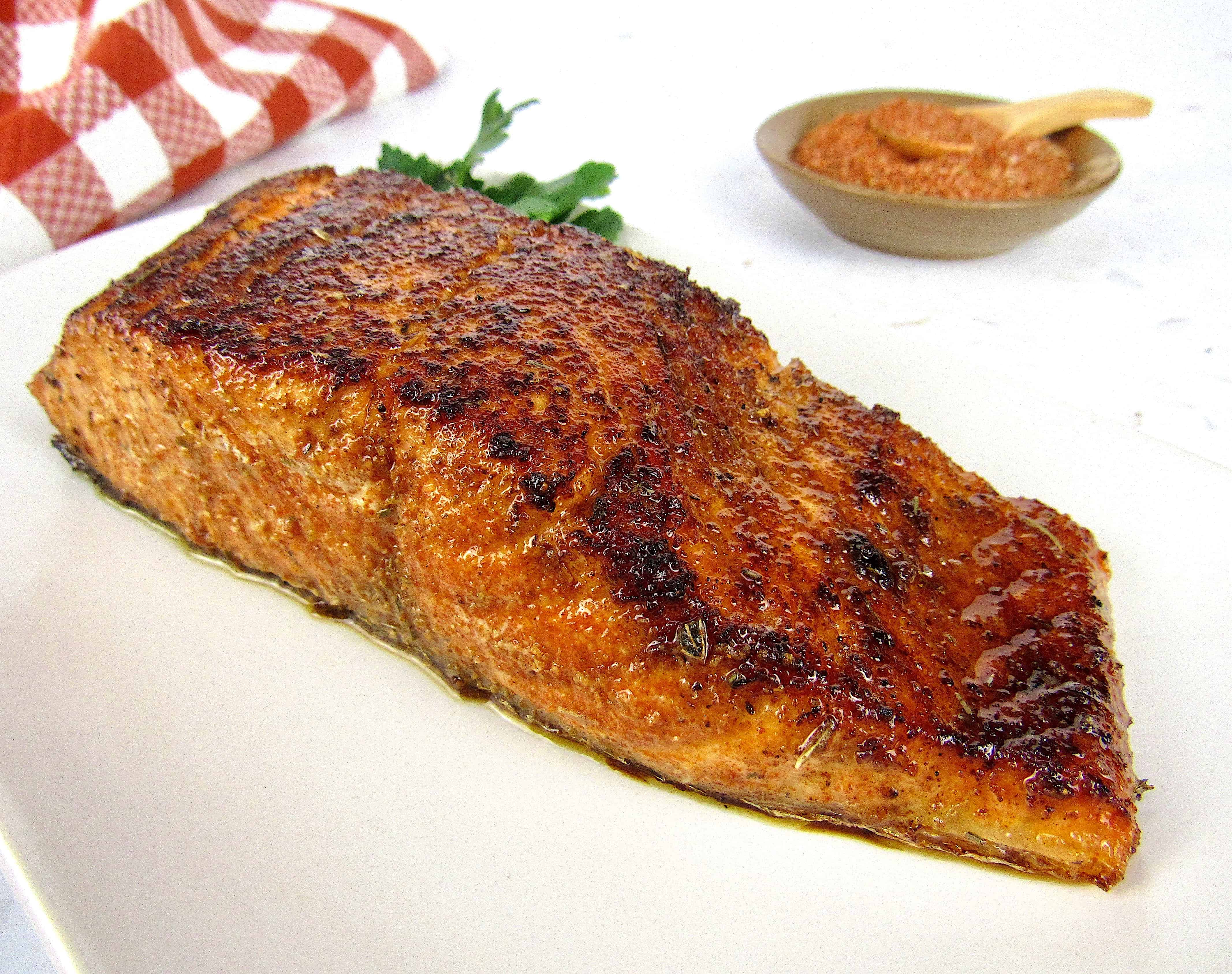blackened salmon on a plate with spices in the background