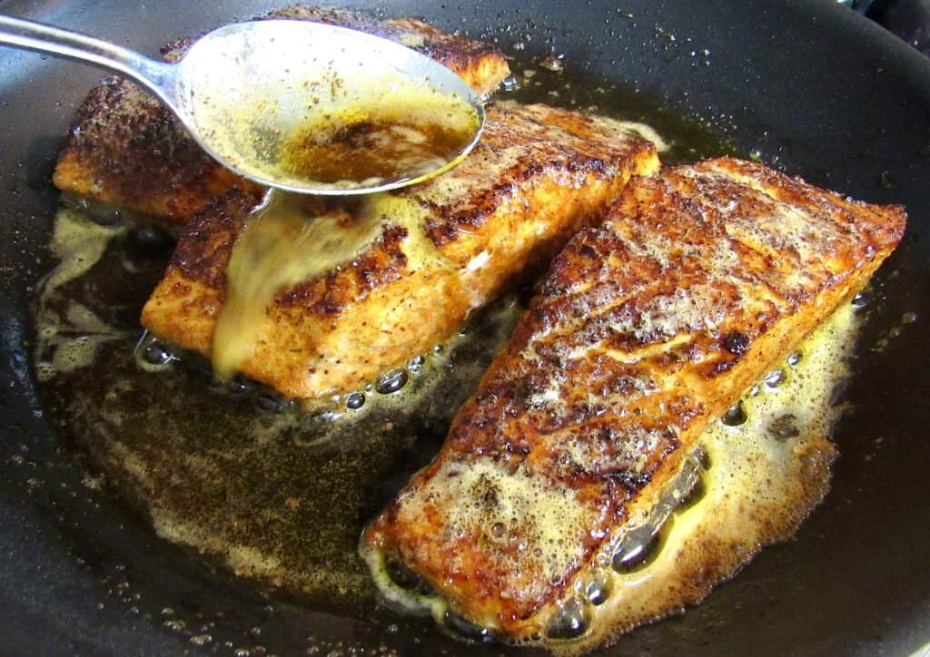 3 pieces of blackened salmon cooking in skillet with butter spooned over top