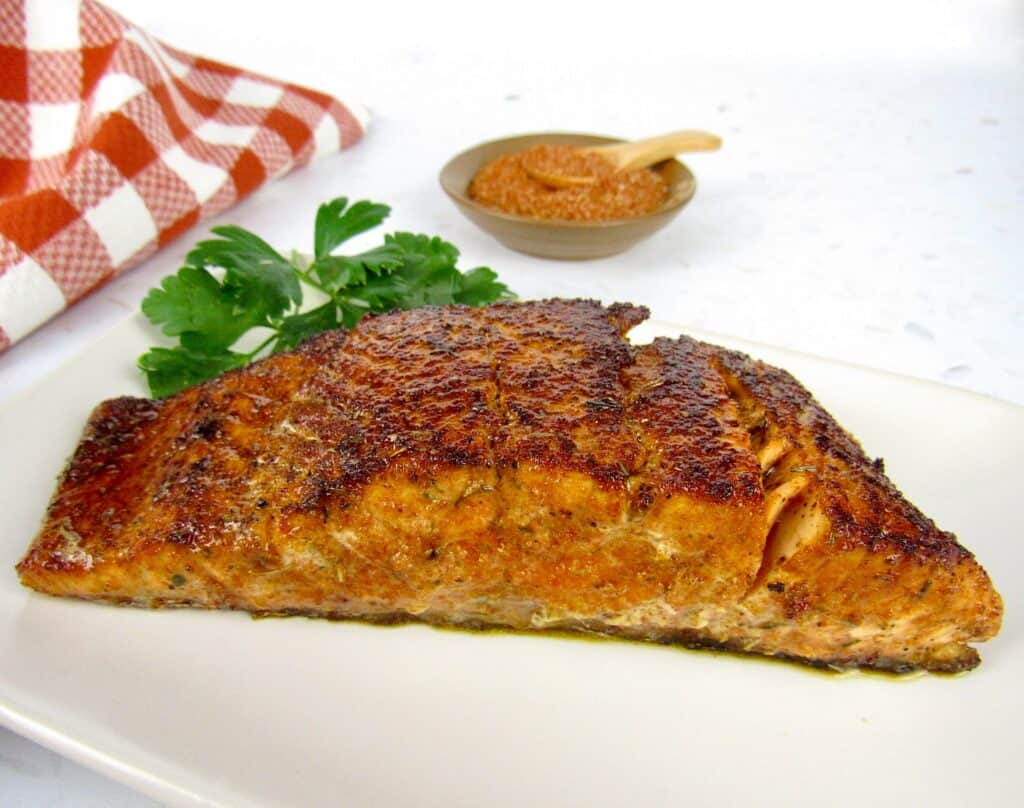 blackened salmon on plate with spices in background