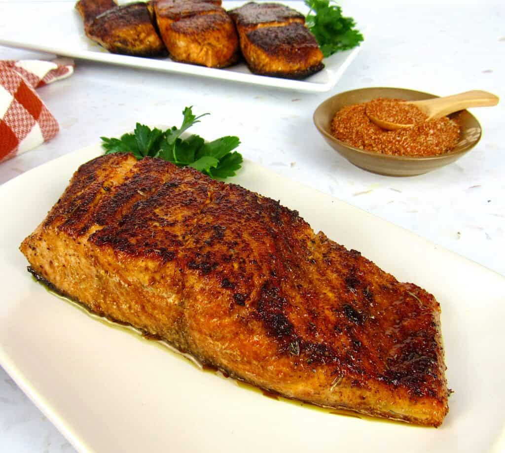 blackened salmon on plate with spices and 3 more pieces in background