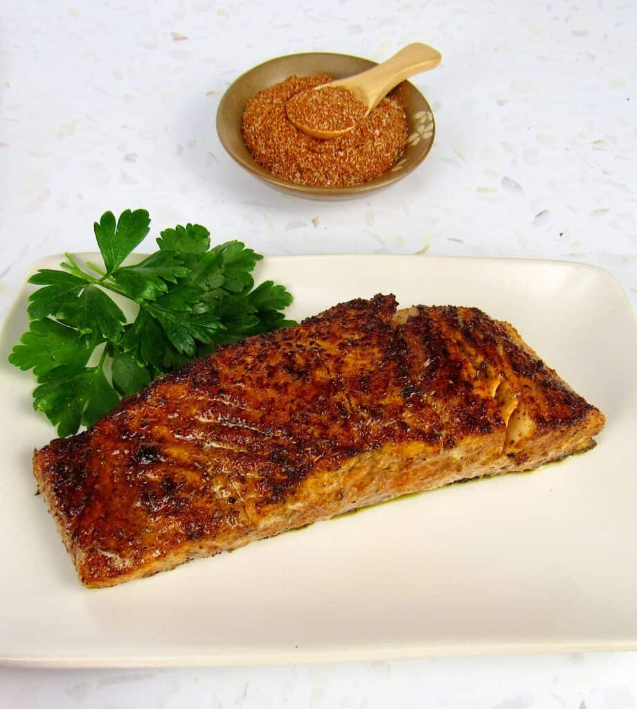 overhead view of blackened salmon on plate with spices in background