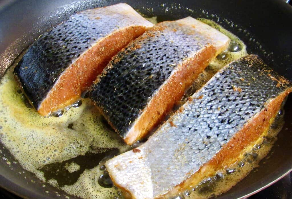 3 pieces of salmon in a skillet cooking skin side up