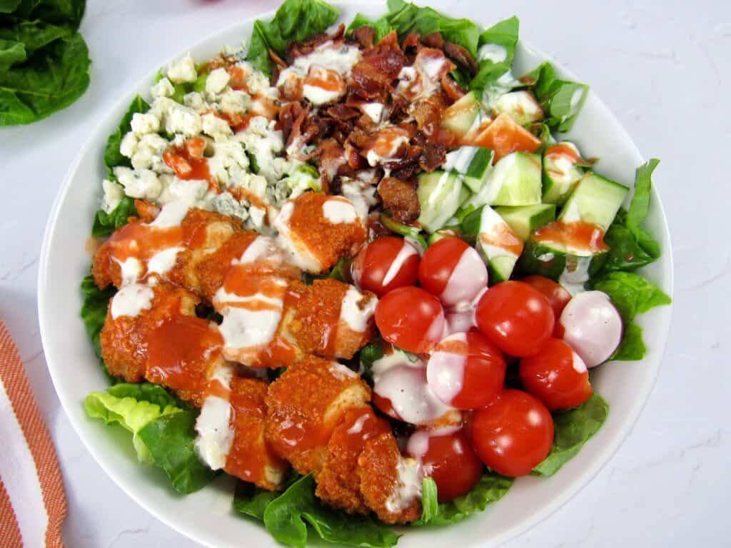 closeup of buffalo chicken salad with blue cheese and hot sauce on top