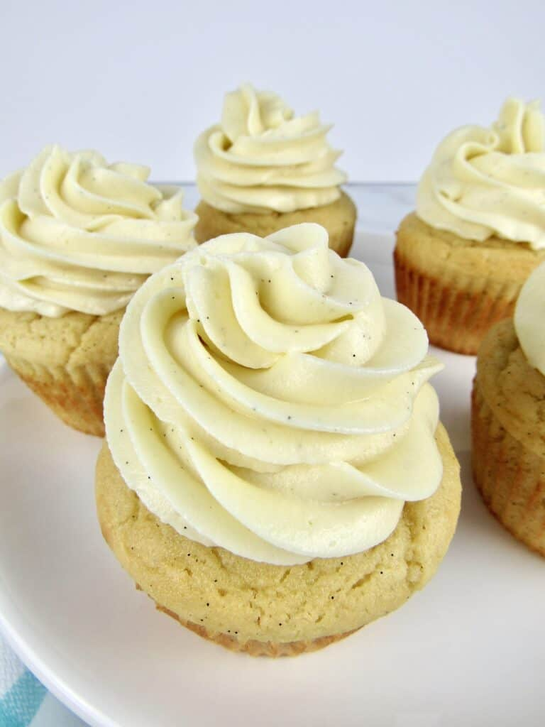 closeup overhead view of vanilla cupcakes on white cake stand